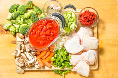 Fresh raw ingredients on the chopping board. Fresh ingredients for chicken cacciatore  on the block ready to cook Royalty Free Stock Photos
