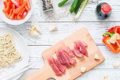 Fresh raw ingredients for cooking Asian spicy pork on white wooden table. Top view Royalty Free Stock Images