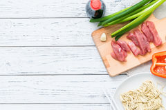 Fresh raw ingredients for cooking Asian spicy pork on white wooden table. Top view, copy space Stock Photos