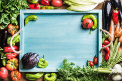 Fresh raw ingredients for healthy cooking or salad making with blue wooden tray in center, top view, copy space. Fresh raw vegetable ingredients for healthy Stock Image