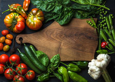 Fresh raw ingredients for healthy cooking or salad making with dark wooden cutting baoard in center, top view, copy Royalty Free Stock Photos