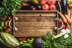 Fresh raw ingredients for healthy cooking or salad making with rustic wooden tray in center, top view, copy space. Fresh raw vegetable ingredients for healthy Royalty Free Stock Images