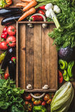 Fresh raw ingredients for healthy cooking or salad making with rustic wooden tray in center, top view, copy space. Fresh raw vegetable ingredients for healthy Stock Images