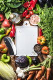Fresh raw ingredients for healthy cooking or salad making with white ceramic board in center, top view, copy space. Fresh raw vegetable ingredients for healthy Stock Photography
