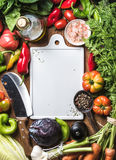Fresh raw ingredients for healthy cooking or salad making with white ceramic board in center, top view, copy space. Fresh raw vegetable ingredients for healthy Royalty Free Stock Photo
