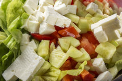 Fresh raw ingredients for salad and white cheese. Fresh raw ingredients and romanian white cheese telemea for salad in bowl Royalty Free Stock Photography