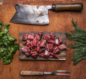 Fresh raw lamb chop on a cutting board for meat cleaver Meat fork herbs top view close up  on wooden rustic background Royalty Free Stock Photography