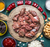 Fresh raw lamb with prunes part of the red pepper onion tomato paste canned chickpeas on a cutting board on wooden rustic backgrou Stock Photography