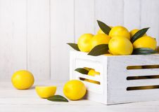 Fresh raw lemons in white wooden box with leaves. On wooden background Royalty Free Stock Images