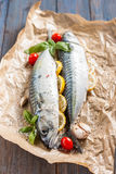 Fresh raw mackerel with lemon, tomatoes and spices on parchment. Preparing to bake. Fresh raw mackerel with lemon, garlic and tomatoes, prepared for baking in Stock Photography