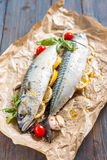 Fresh raw mackerel with lemon, tomatoes and spices on parchment. Preparing to bake. Fresh raw mackerel with lemon, garlic and tomatoes, prepared for baking in Royalty Free Stock Photo