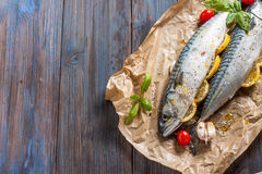 Fresh raw mackerel with lemon, tomatoes and spices on parchment. Preparing to bake. Fresh raw mackerel with lemon, garlic and tomatoes, prepared for baking in Stock Photo