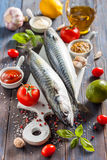 Fresh raw mackerel with lemon, tomatoes and spices on parchment. Preparing to bake. Fresh raw mackerel with lemon, garlic and tomatoes, prepared for roasting Royalty Free Stock Image