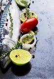 Fresh raw mackerel with tomato and lemon on a black metal pan Royalty Free Stock Photo
