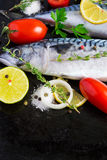 Fresh raw mackerel with tomato and lemon on a black metal pan Stock Photos