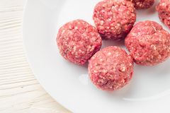 Meat balls from raw beef force-meat on a white plate. Fresh raw meat balls white plate on wooden background, top view Royalty Free Stock Images
