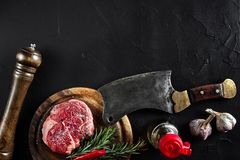 Piece of beef tenderloin, with ax for cutting and chopping meat, spices were cooking - rosemary, pepper, salt, garlic. Fresh raw meat. Beef. Piece of beef Stock Images