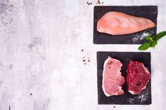 Fresh raw meat - beef, pork and chicken on dark slate cutting board. Lean proteins. Lean proteins. Fresh raw meat - beef, pork and chickenon dark slate cutting Stock Image