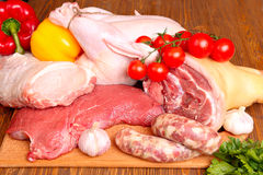 Fresh raw meat - beef, pork, chicken. And vegetables on a wooden background Royalty Free Stock Image