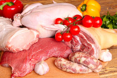 Fresh raw meat - beef, pork, chicken. And vegetables on a wooden background Stock Photo