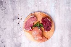 Fresh raw meat - beef, pork and chicken on a wooden background. Lean proteins. Fresh raw meat - beef, pork and chicken on a wooden board on a concrete Royalty Free Stock Photography