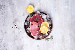 Fresh raw meat - beef and pork on a wooden plate with lemon slice and ice. Lean proteins. Fresh raw meat - beef and pork on a wooden plate with lemon slice and Royalty Free Stock Images