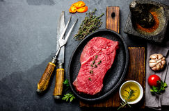Fresh raw meat beef steak. Beef tenderloin, spices, herbs and vintage cutlery. Food background with copy space Stock Images