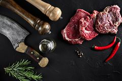 Piece of beef tenderloin, with ax for cutting and chopping meat, spices were cooking - rosemary, pepper on old black. Fresh raw meat. Beef steak. Piece of beef Royalty Free Stock Images