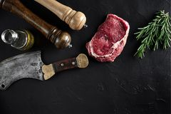 Piece of beef tenderloin, with ax for cutting and chopping meat, spices were cooking - rosemary, pepper on old black. Fresh raw meat. Beef steak. Piece of beef Stock Photos