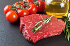 Fresh raw meat beef steak. With with rosemary, tomatoes and olive oil on the black slate surface Royalty Free Stock Images