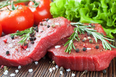 Fresh raw meat beef steak. Fresh raw beef steak with spice and vegetable on brown wooden table Royalty Free Stock Images