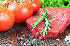 Fresh raw meat beef steak. Fresh raw beef steak with spice and vegetable on brown wooden table Royalty Free Stock Photo