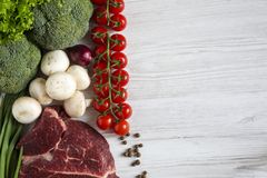 Fresh raw meat beef steak with spices, cherry tomatoes, health f. Fresh raw meat beef steak with spices, cherry tomatoes, health. Flat lay Stock Image