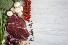 Fresh raw meat beef steak with spices, cherry tomatoes, health f. Fresh raw meat beef steak with spices, cherry tomatoes, health. Fiat lay Royalty Free Stock Photography