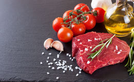 Fresh raw meat beef steak. With with spices, rosemary, tomatoes and olive oil on the black slate surface Stock Photography