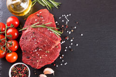 Fresh raw meat beef steak. With with spices, rosemary, tomatoes and olive oil on the black slate surface. Top view Stock Image