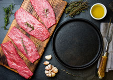 Fresh raw meat beef steaks. Beef tenderloin in cast iron pan on wooden board, spices, herbs, oil on slate gray background. Food ba. Ckground with copy space Royalty Free Stock Photos