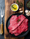 Fresh raw meat beef steaks. Beef tenderloin in cast iron pan on wooden board, spices, herbs, oil on slate gray. Background. Food background with copy space Royalty Free Stock Photos
