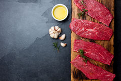 Fresh raw meat beef steaks. Beef tenderloin on wooden board, spices, herbs, oil on slate gray background. Food background with cop Stock Image