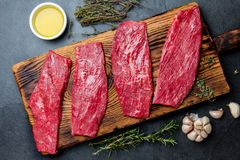 Fresh raw meat beef steaks. Beef tenderloin on wooden board, spices, herbs, oil on slate gray background. Food cooking background. Concept Stock Images