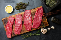 Fresh raw meat beef steaks. Beef tenderloin on wooden board, spices, herbs, oil on slate gray background. Food cooking background. Concept Stock Photography