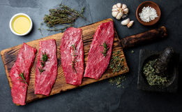 Fresh raw meat beef steaks. Beef tenderloin on wooden board, spices, herbs, oil on slate gray background. Food cooking background. Concept Royalty Free Stock Images