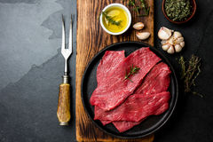 Fresh raw meat beef steaks. Beef tenderloin in cast iron pan on wooden board, spices, herbs, oil on slate gray background. Food ba. Ckground with copy space Stock Image