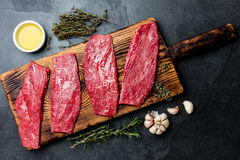 Fresh raw meat beef steaks. Beef tenderloin on wooden board, spices, herbs, oil on slate gray background. Food cooking background. Concept Royalty Free Stock Photos