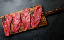 Fresh raw meat beef steaks. Beef tenderloin on wooden board, spices, herbs, oil on slate gray background. Food cooking background. Concept Royalty Free Stock Image