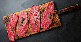 Fresh raw meat beef steaks. Beef tenderloin on wooden board, spices, herbs, oil on slate gray background. Food cooking. Background concept Stock Images