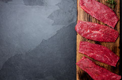 Fresh raw meat beef steaks. Beef tenderloin on wooden board, spices, herbs, oil on slate gray background. Food background with cop Stock Photo