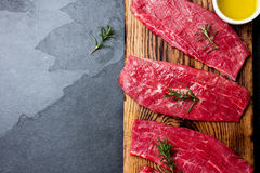 Fresh raw meat beef steaks. Beef tenderloin on wooden board, spices, herbs, oil on slate gray background. Food background with cop Royalty Free Stock Image