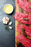 Fresh raw meat beef steaks. Beef tenderloin on wooden board, spices, herbs, oil on slate gray background. Food background with cop Royalty Free Stock Photography
