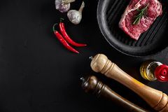 Fresh raw meat. Beef Tenderloin and marbled beef steaks on grill pan and frying board with seasoning, black background. Top view. Still life. Copy space. Flat Stock Images